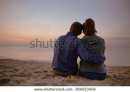 couple sitting on beach and looking on sea - stock photo
