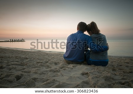 couple sitting on beach and looking on sea