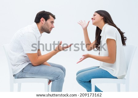 Couple sitting on chairs arguing on white background - stock photo