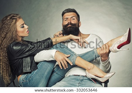 Couple sitting on chairs young woman wearing black leather jacket jeans diamante high heels pulling beard of unshaven man he playing legs of girl like guitar on grey background, horizontal picture - stock photo