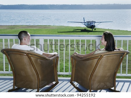 Couple sitting on deck with airplane in yard