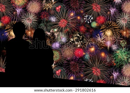 Couple sitting on floor and watching the Fireworks Celebration at night  - stock photo