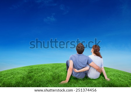 Couple sitting on floor together against green hill under blue sky - stock photo