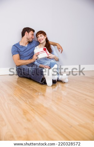 Couple sitting on floor together with a present - stock photo