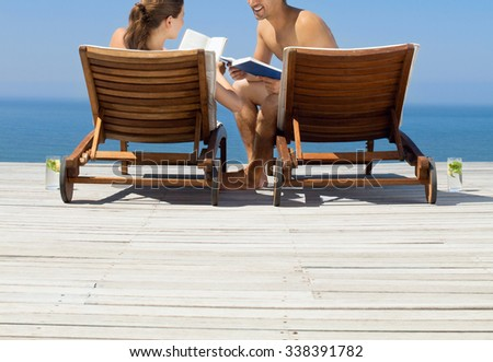 Couple sitting on lounge chairs at poolside - stock photo