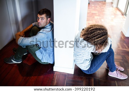Couple sitting on opposite sides of the wall and feeling sad - stock photo