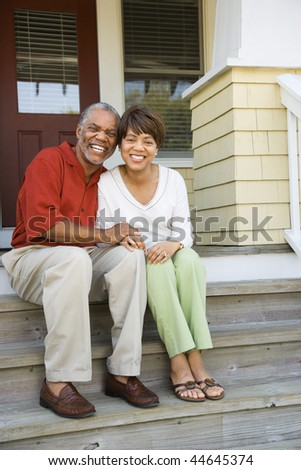 Couple sitting on outdoor steps of home smiling. Vertically framed shot. - stock photo