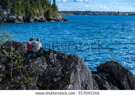 Couple sitting on rocks looking out over the lake.