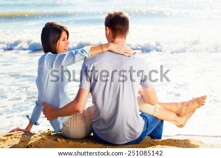 Couple Sitting on Sand at the Beach looking the sea - stock photo