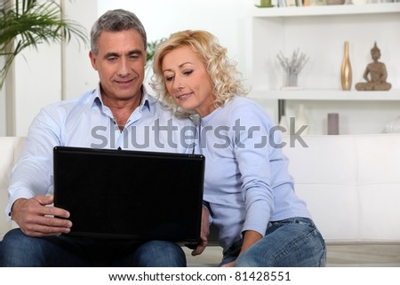 Couple sitting on sofa looking at laptop - stock photo