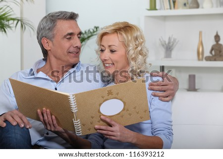 couple sitting on sofa skimming through family album - stock photo