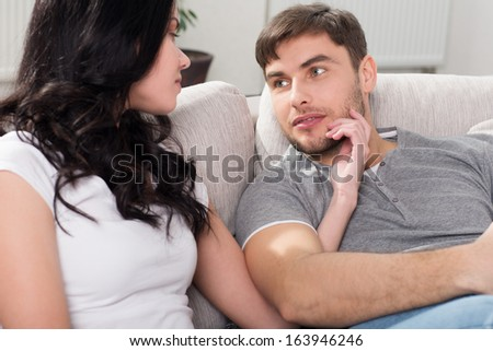 couple sitting on the couch in the living room, looking lovingly at each other