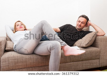 Couple sitting on the couch or sofa after a dispute. Upset wife and husband at home concept - stock photo