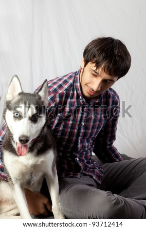 Couple sitting on the floor with their pet Husky dog