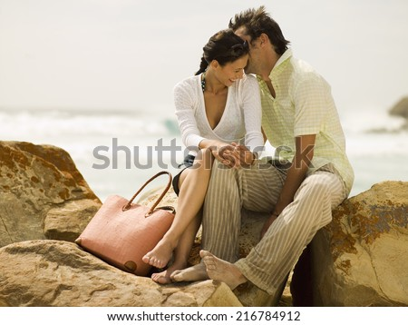 Couple sitting on the rocks at a beach. - stock photo