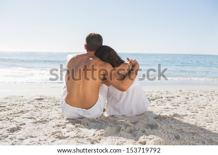 Couple sitting on the sand watching the sea at the beach - stock photo