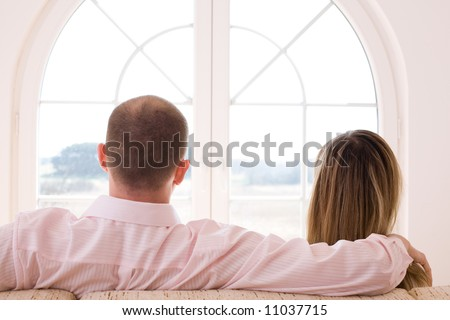 Couple sitting on the sofa in front of window/ Window on the world / freedom / new time - stock photo
