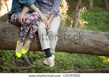 Couple sitting on tree trunk