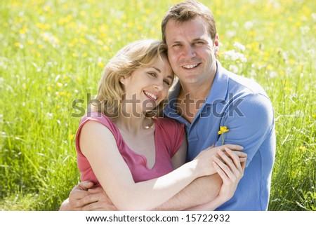 Couple sitting outdoors holding flower smiling - stock photo