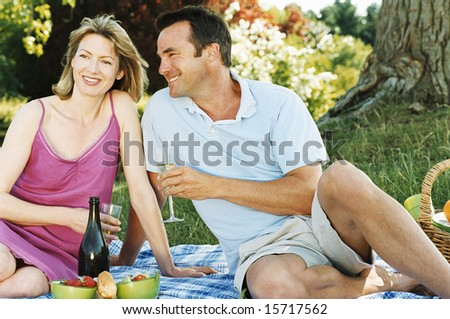 Couple sitting outdoors with picnic smiling - stock photo