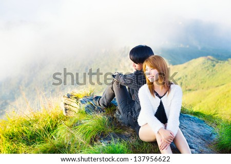 Couple sitting over Mountains - stock photo