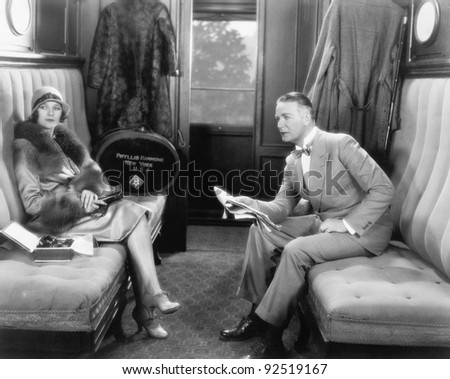 Couple sitting together in a compartment of a train