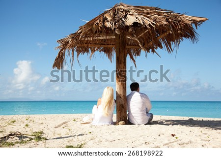 couple sitting under palm umbrella and looking at the sea - stock photo