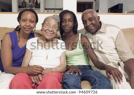 Couple sitting with their teenage daughter and mother in-law on a couch - stock photo