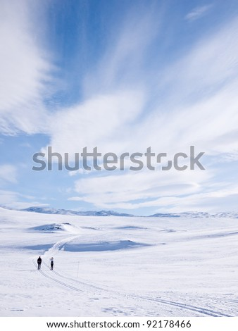 Couple skiing in a groomed curved double ski track with mountain summits and a characteristic cloud formation in the background in the norwegian mountains at easter - stock photo