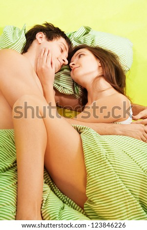 Couple sleeping together in bed with smile on their faces and attractive woman touching husbands face - stock photo