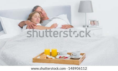 Couple sleeping with breakfast tray on bed at home in bedroom - stock photo