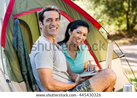 Couple smiling and holding a laptop on their camp site