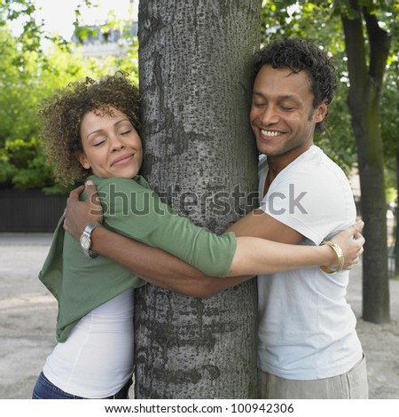 Couple smiling and hugging tree