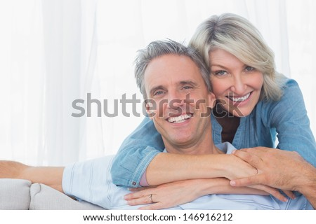 Couple smiling at the camera at home in living room - stock photo
