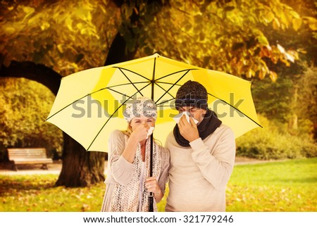 Couple sneezing in tissue while standing under umbrella against trees and meadow in the park - stock photo