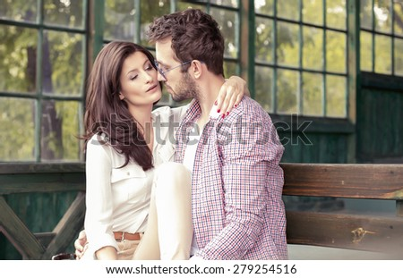 couple snuggling on a bench
