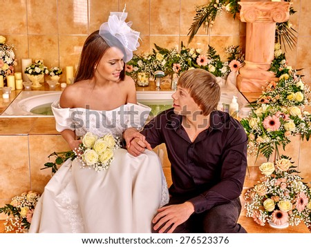 Couple spend wedding night  at luxury spa.  She takes off her dress. - stock photo