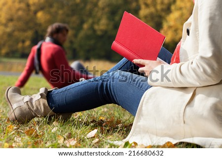 Couple spending free time in autumn by relaxing in the park