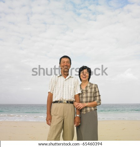 Couple standing arm in arm at beach