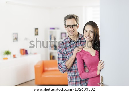 couple standing at front door to invite people at home - stock photo