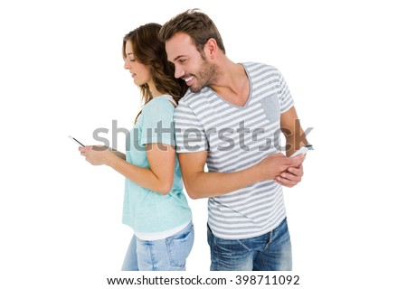 couple standing back to back and man looking at womans mobile phone on white background - stock photo