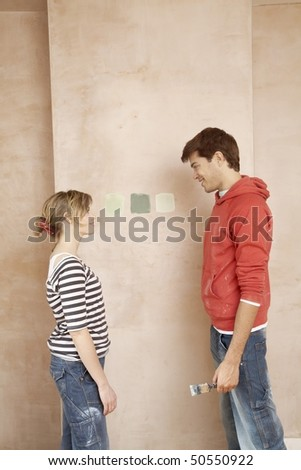 Couple standing face to face, choosing paint colour samples on wall - stock photo