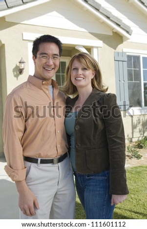 Couple standing in front of a new house - stock photo