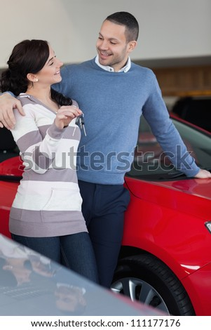 Couple standing next to a car while holding keys - stock photo