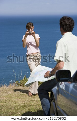 Couple standing on clifftop overlooking Atlantic Ocean, woman photographing man with map beside car - stock photo