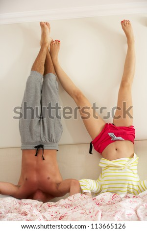 Couple Standing On Head In Bed - stock photo