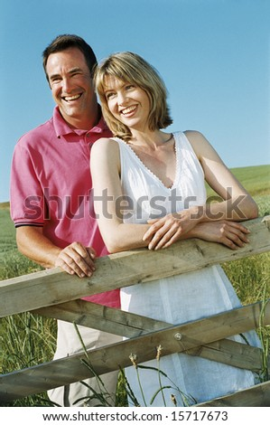 Couple standing outdoors by fence smiling - stock photo