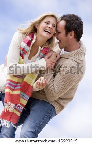 Couple standing outdoors smiling - stock photo