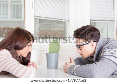 couple staring at each other across the table at home - stock photo
