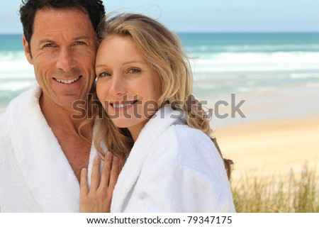 Couple stood by the sea wearing bathrobes - stock photo